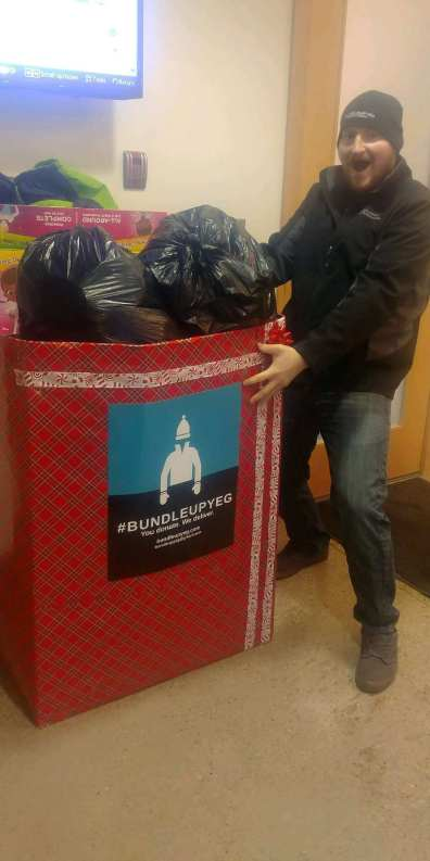 Volunteer Cody picks up the first big haul of clothing donations from 102.3 Now! Radio.